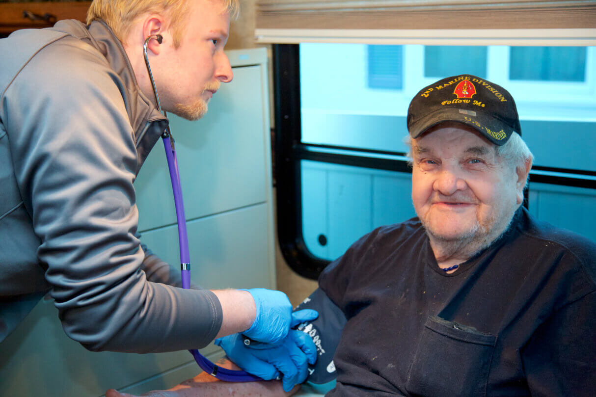 Student checking blood pressure in the Care Van.