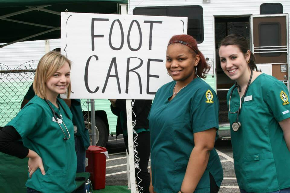 Photo of three female nursing students outside of the Elms caRe vaN. A sign reading