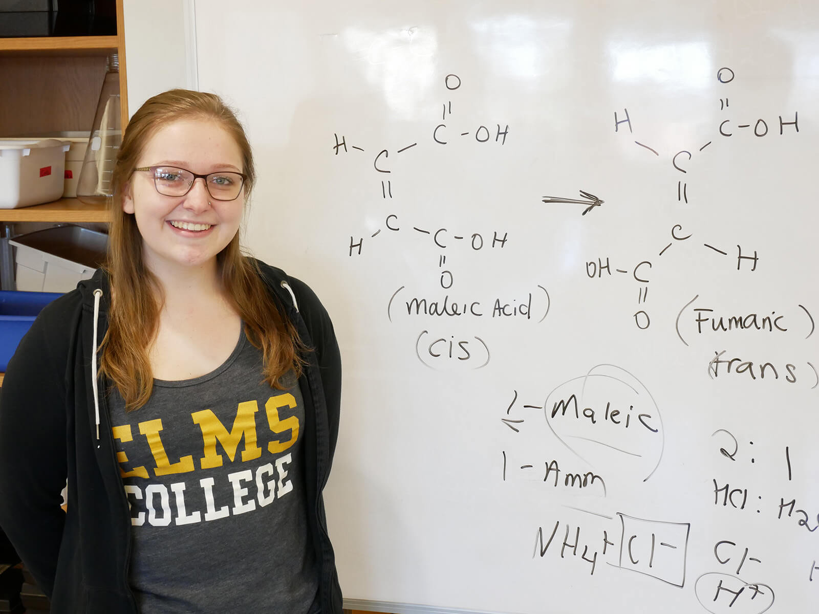 Photo of ElmSTEM scholar and chemistry major April Thresher in front of a white board.