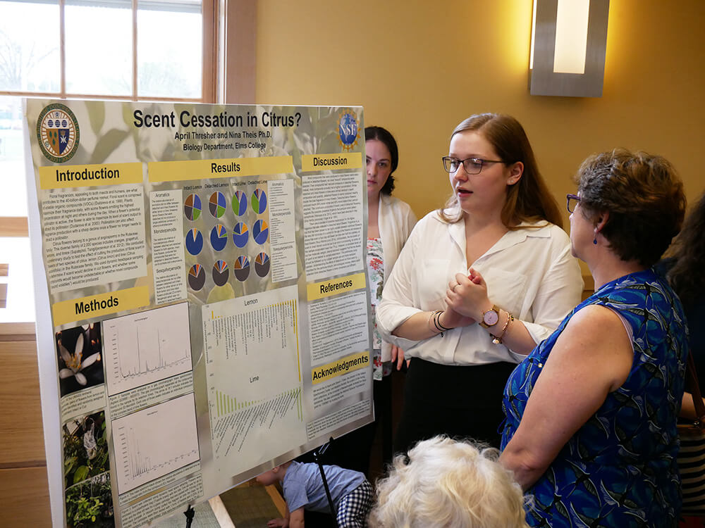 Photo of ElmSTEM scholar April Thresher presenting a research poster.