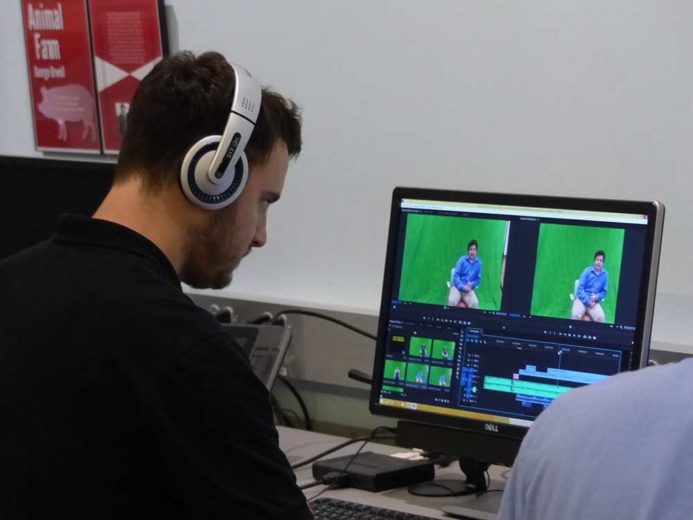 Photo of a student editing video using a green screen or chroma key effect in the CIT (Computer Information Technology) lab in the Lyons Center