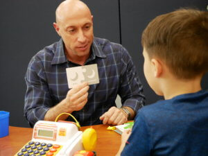 Photo of a grad student in the ASD-ABA program working with a student