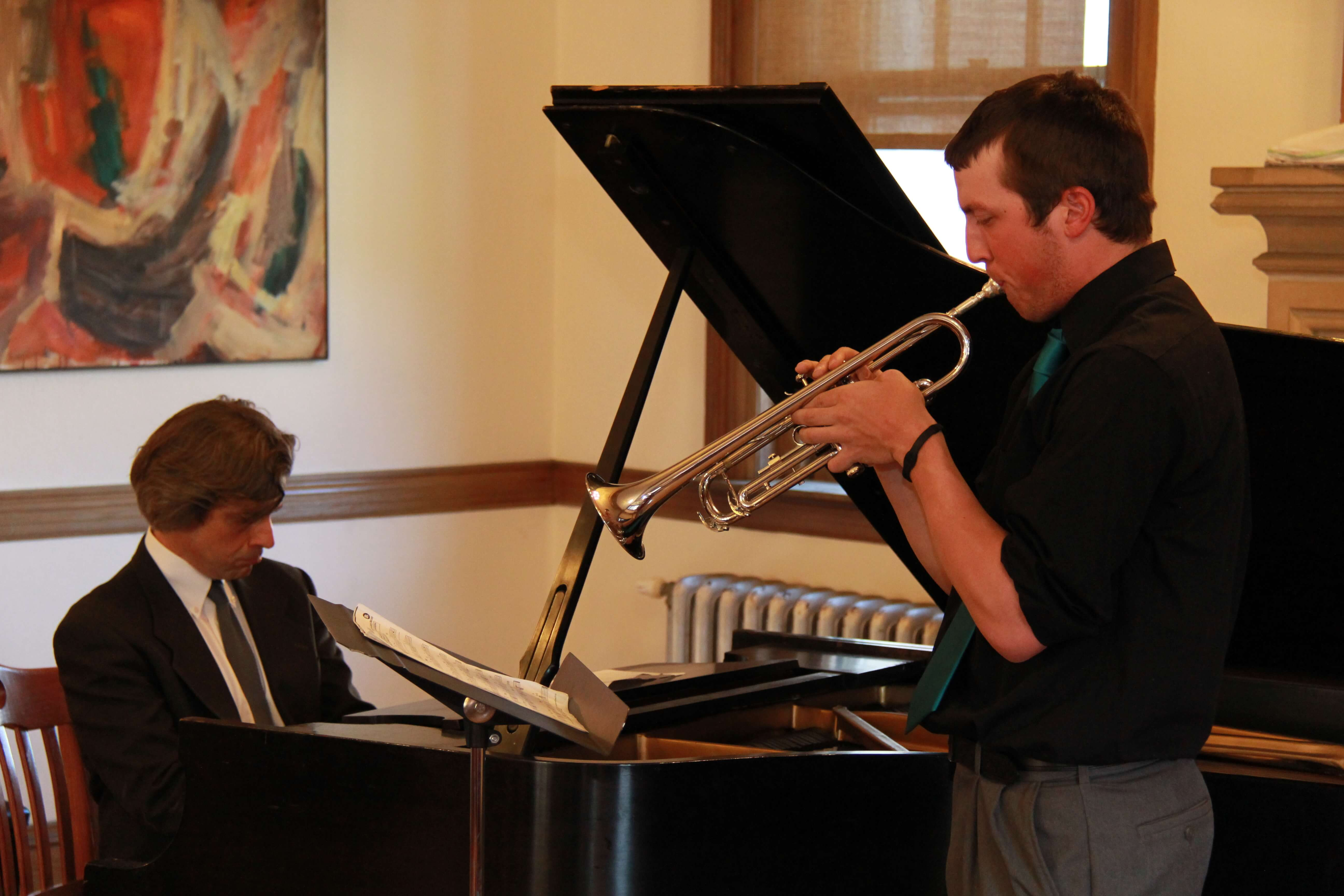 Photo of Professor Chris Bakriges playing the piano and a student playing the trumpet