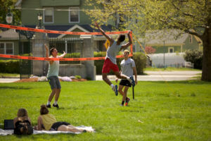 Photo of students playing volleyball on the lawn in front of Berchmans Hall