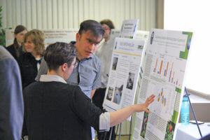 Photo of students discussing work at the annual experiential learning showcase