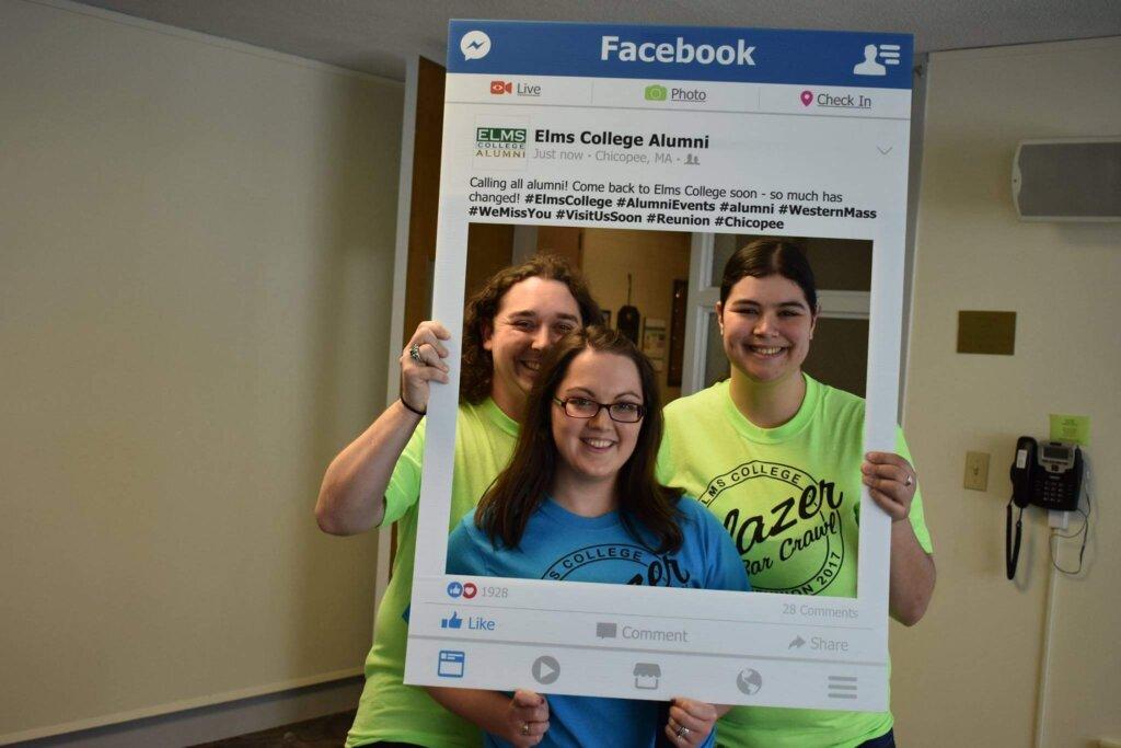 Alumni standing in an Elms College Alumni Facebook photo frame.