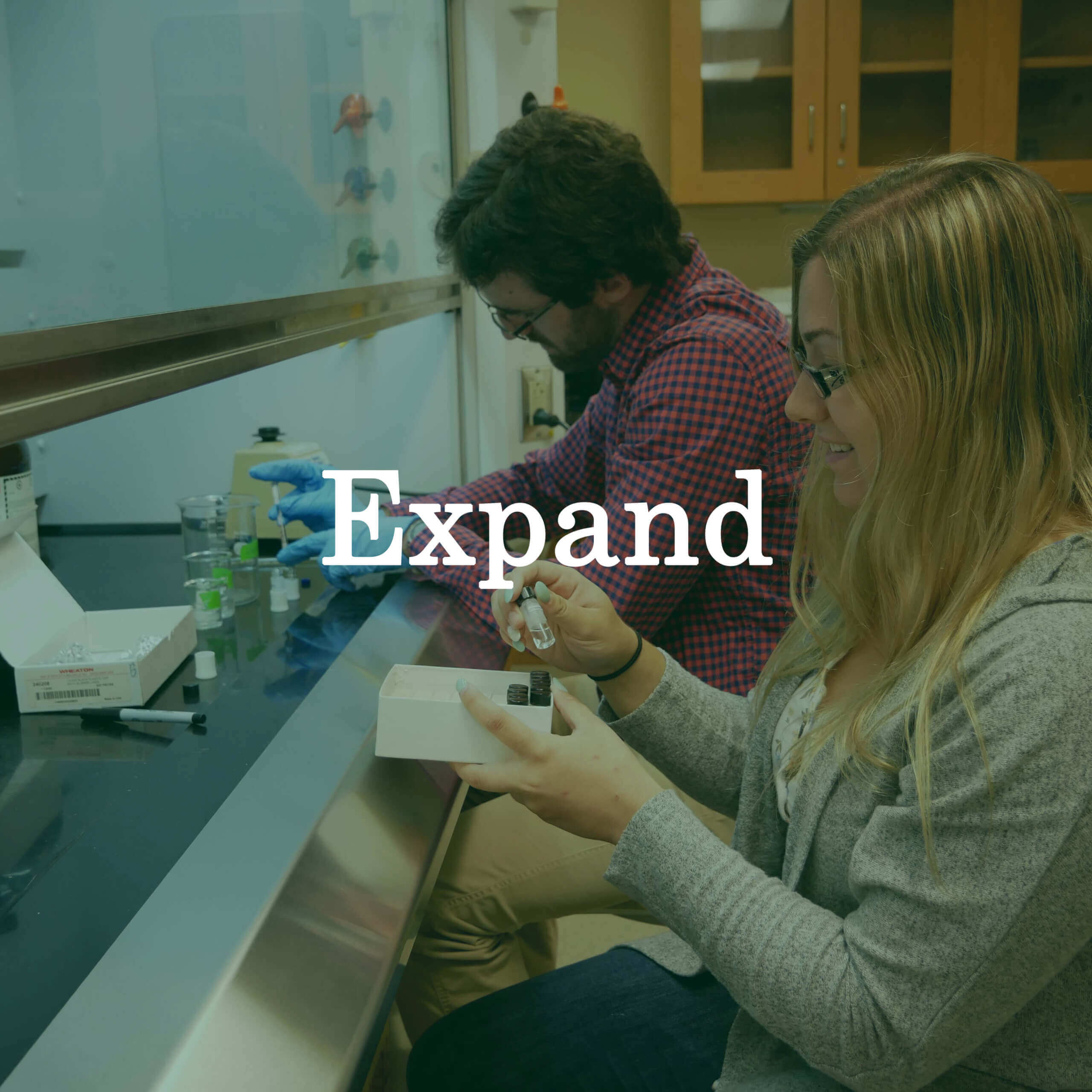 "Photo of students working at a lab bench with a text overlay that reads ""Expand."""